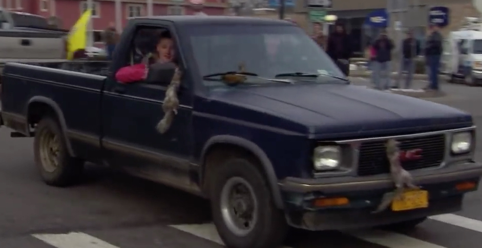 Hunters hang dead squirrels on hood of truck and out the window