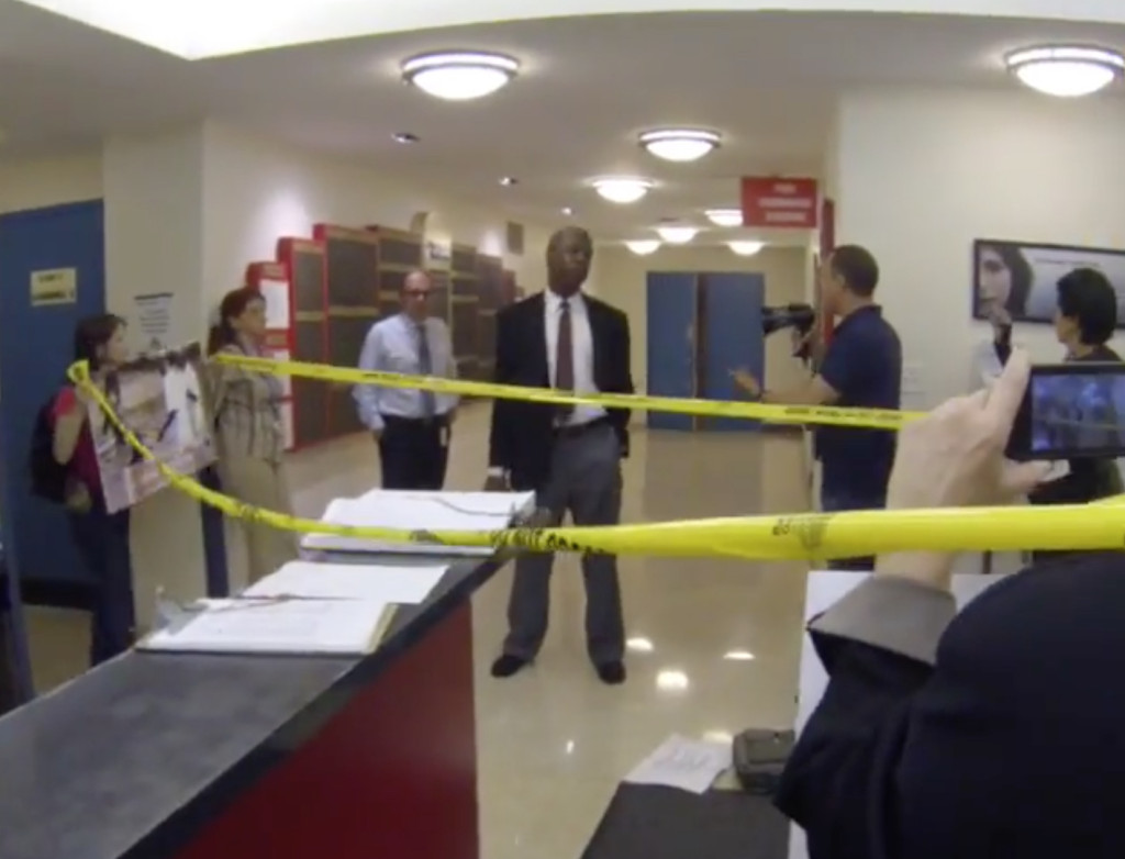 Activists unroll police tape to convey the message that the NYBC is a crime scene