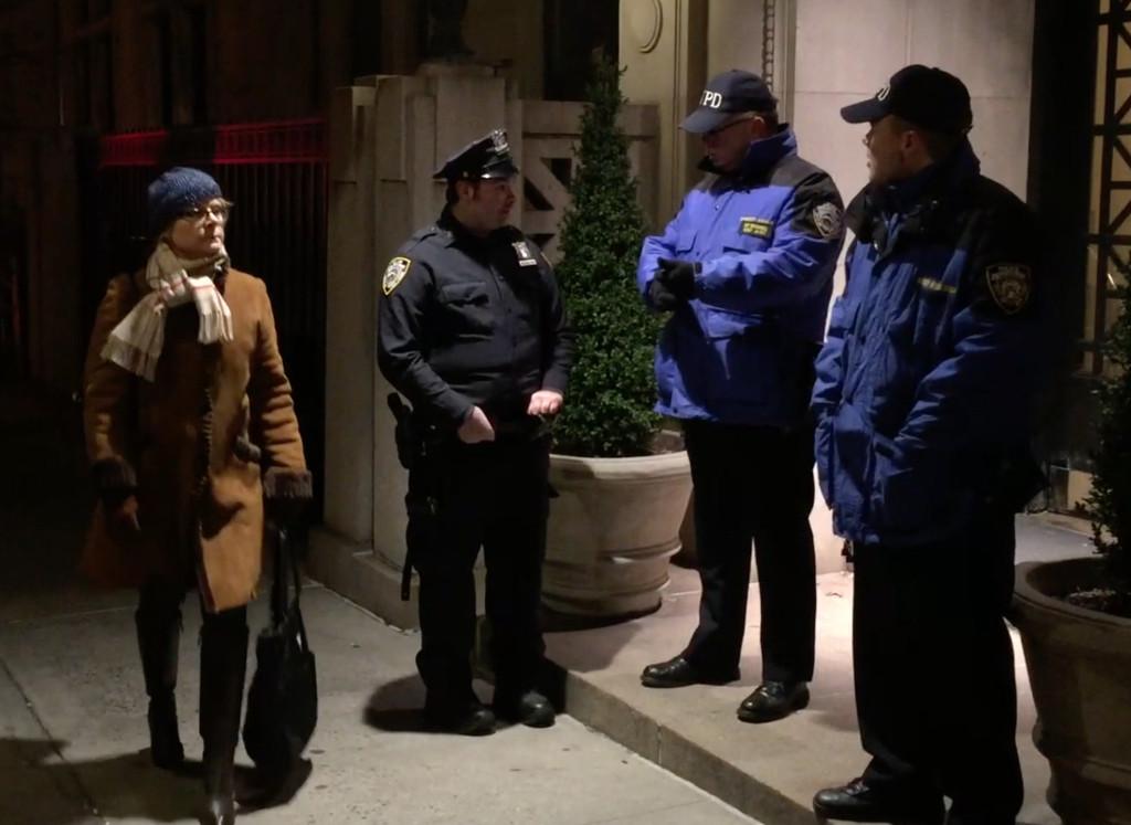 At least a dozen police officers and private security guards were stationed inside and outside of Michael Hodin's exclusive Upper West Side apartment building.