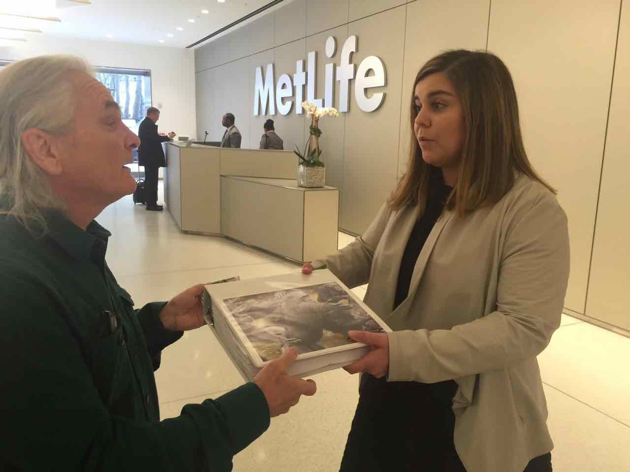Primatologist Bob Ingersoll delivers petitions to a MetLife representative.