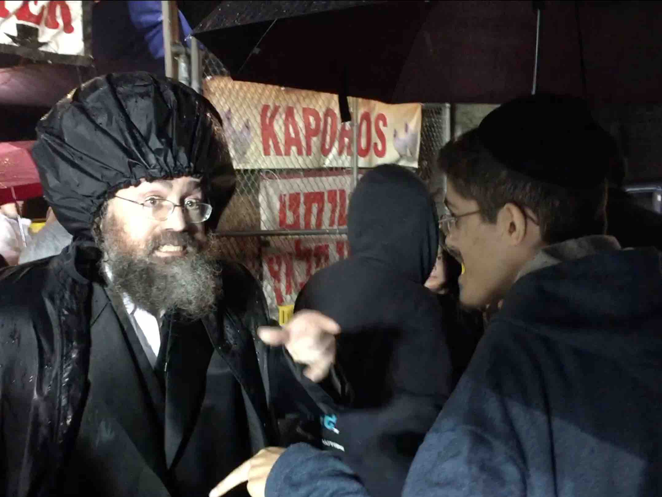 Shimon Shuchat, who was born into the Hassidic community but has since left, encourages a Kaporos practitioner to swing coins instead of live chickens.